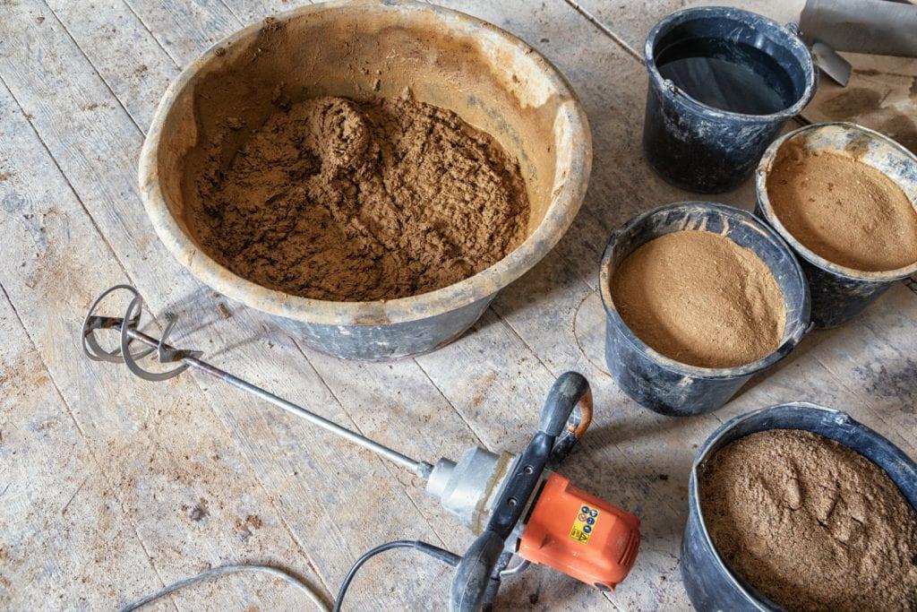 Verschiedene Mischkübel mit fertigem Lehmputz, Wasser und Rohmaterial - daneben liegt ein Mörtelmischer